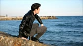 не : Handsome fashionable young man at the seaside along the shore overlooking the ocean or sea with his black leather jacket