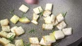rozmarýna : White bread croutons toasting in frying pan with extra virgin olive oil and rosemary