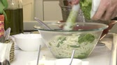 песто : Chef pouring basil pesto in a bowl full of pasta