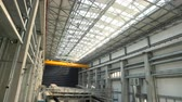Hangar in a shipyard, with a view of the hull of a maxi yacht