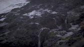 Slow-motion footage of water dripping down from the sea wall in Depoe Bay with waves crashing in the background during a storm. Stock Footage