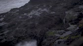 Slow-motion footage of waves crashing against the rock wall at Depoe Bay, OR and shooting up through a crevasse. Stock Footage