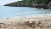 coming in : Sandcastles on the beach, gentle waves lapping in a rugged rocky cove Stock Footage