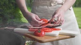 suluguni : Housewife places sliced tomatoes into the raw fish before cook it, carp fish on the board, cooking fish meals outdoors, seafood on the grill, barbecue and fire
