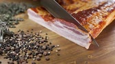 бекон : Chef cuts pieces of smoked bacon by sharp knife on the wooden board, cooking meat, meals with meat products, pork