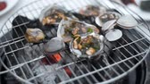 racks : Mussels is roasted in the sauce on the open fire of grill, cooking of shellfish outdoors, seafood barbecue, grilling the seafood Stock Footage