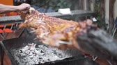 laosz : Grilled crocodile on the open fire at sea food restaurant, exotic meals in Viethnam, food of the asian cuisine, raw crocodile meat, exotic meal Stock mozgókép