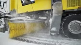 coal mine : Heavy wheel machinery removes snow from the road with big massive rotating brush in the snowy weather, special machinery for roads cleaning, snow and ice removal Stock Footage