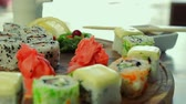 delicadeza : Dolly shot of delicious sushi rolls on wooden plate with wasabi and ginger