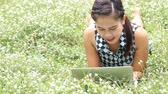 lawn : Smiling women use laptop computer while lying in park Stock Footage