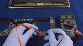 Engineer in the blue gloves carries out diagnostics with the probes of tester. Velvet background. Close-up