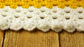yarn : Needlework. Colorful woolen bedspread crocheted on a wooden background. Close-up. Stock Footage