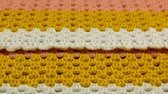 crochê : Needlework. Colorful woolen bedspread crocheted on a wooden background. Close-up. Stock Footage