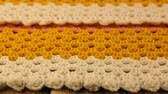 編み : Needlework. Colorful woolen bedspread crocheted and three crochet hooks on a wooden background. Close-up.