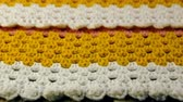 Needlework. Colorful woolen bedspread crocheted and three colored crochet hooks on a wooden background. Close-up.