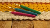 編み : Needlework. Three colored crochet hooks on a colorful crocheted woolen bedspread. Close-up. 動画素材