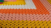 編み : Needlework. Three colored crochet hooks and skeins of color yarn on a colorful crocheted woolen bedspread. Close-up.