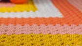 Needlework. Three colored crochet hooks and skeins of color yarn on a colorful crocheted woolen bedspread. Close-up.