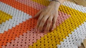 Needlework. The master by hand checks the quality of the colorful crocheted woolen bedspread. Стоковые видеозаписи