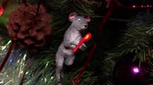 noel kartı : New Years composition, Christmas decorations. Christmas toy of a gray rat hangs on a decorated Christmas tree on the background of a blinking garland. Close-up Stok Video