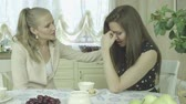 успокоить : Portrait of two sad young women having tea at dining table.  Two Caucasian friends have a serious conversation at home. Beautiful interior design.