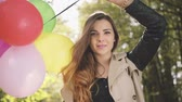 móda : Cheerful brunette girl with colorful balloons smiling in autumn park.