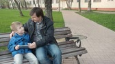 handheld : Father teaching his cute young son to use a tablet