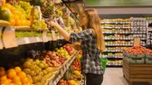 cartn corrugado : Beautiful young woman shopping for fruits products at a supermarket Stock Footage