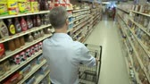 półka : Pushing a shopping cart in a grocery store