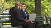 dyskusja : Two business men discuss the details of an upcoming presentation in the informal setting of the park.