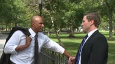 profit : Two young businessmen hold an informal conversation in a city park. Stock Footage