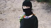 Girl in the black mask look at the camera and holding the flowers Стоковые видеозаписи