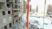 quadcopter : Crane with a cement hose stands near the building on the construction site