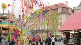 art : PRAGUE, CZECH REPUBLIC: APRIL 2014 - Easter markets - easter decorated tree with shops and people in background