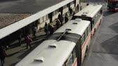 weather : Bus in depot and people leave bus.