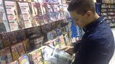 manchete : man looks at a magazine in a newspaper shop Vídeos