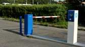 entrada da garagem : barrier in the parking lot - machine on parking tickets - bushes in background