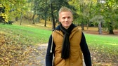 moda : man walking in autumn park - man smiles (happy) - sun rays - (man looks into the camera)