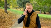 autumn : man on the phone (man calling by smartphone) - man walking in autumn park - man smiles (happy) Stock Footage