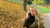 autumn : woman on the phone (woman calling by smartphone) - woman walking in autumn park - woman smiles (happy)