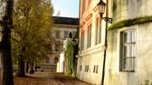 weather : old street - urban buildings - autumn trees - sun rays - people in background
