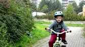 Child (a little boy) rides bike and smiles - in the background houses and nature (grass and trees)