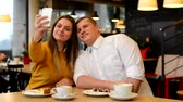 telemóvel : happy couple are photographing smartphone (selfie) in cafe - coffee and cake