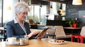 kaka : business middle aged woman works on tablet in cafe - coffee and cake Stockfilm