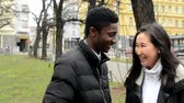gag : happy couple laugh and talk (conversation) - urban street with cars in the city - park - black man and asian woman Stock Footage