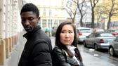 female : Unhappy couple are offended - black man and asian woman - urban street with cars