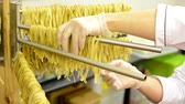 drying rack : A worker takes down dried pasta from stand - closeup