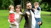 man elstv : family middle couple in love, cute girl and small boy shows thumb on disagreement in the park Stock Footage