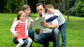 man elstv : family middle couple in love, cute girl and small boy read document in the park
