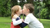 sister : children siblings - boy and girl give a kiss in park